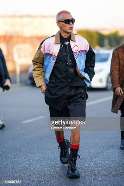 Evan Mock skateboarder wears sunglasses a Prada jacket a black Prada shirt a mini bag black shorts red and black socks leather shoes outside Prada...