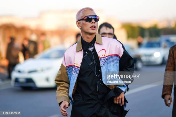 Evan Mock skateboarder wears sunglasses a Prada jacket a black Prada shirt a mini bag outside Prada during Milan Fashion Week Menswear Fall/Winter...