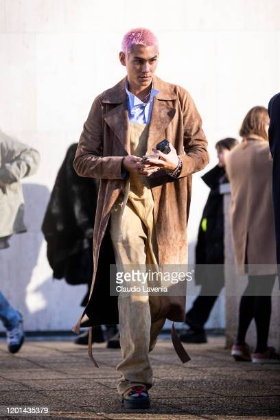 Evan Mock wearing a striped shirt beige overall and brown coat is seen outside the Loewe show during the Paris Fashion Week Menswear F/W 20202021 on...