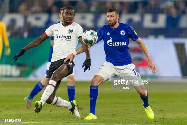 Evan N'Dicka of Eintracht Frankfurt and Daniel Caligiuri of FC Schalke 04 battle for the ball during the Bundesliga match between FC Schalke 04 and...