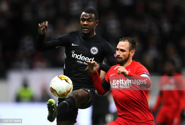 Evan N'Dicka of Eintracht Frankfurt controls the ball with pressure from Andreas Ulmer of RB Salzburg during the UEFA Europa League round of 32 first...