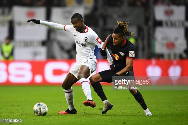 Evan N'dicka of Eintracht Frankfurt is challenged by Christopher Nkunku of RB Leipzig during the DFB Cup round of sixteen match between Eintracht...