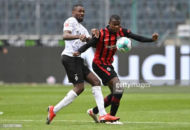 Evan Ndicka of Eintracht Frankfurt is challenged by Marcus Thuram of Borussia Moenchengladbach during the Bundesliga match between Borussia...