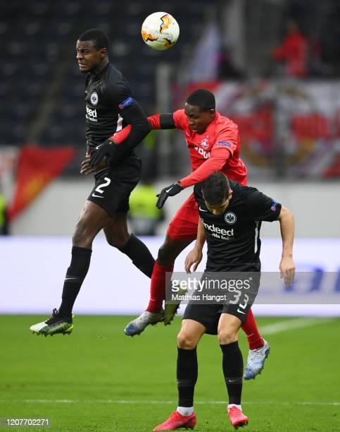 Evan N'Dicka of Frankfurt, Enock Mwepu of Salzburg and Andre Silva of Frannkfurt jump for a header during the UEFA Europa League round of 32 first...