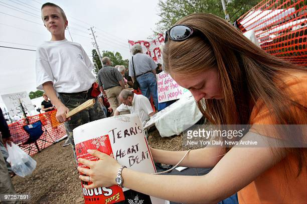 Evan Nee and his sister Kira Black beat a drum representing the heartbeat of Terri Schiavo as they protest the March 18 removal of her feeding tube...