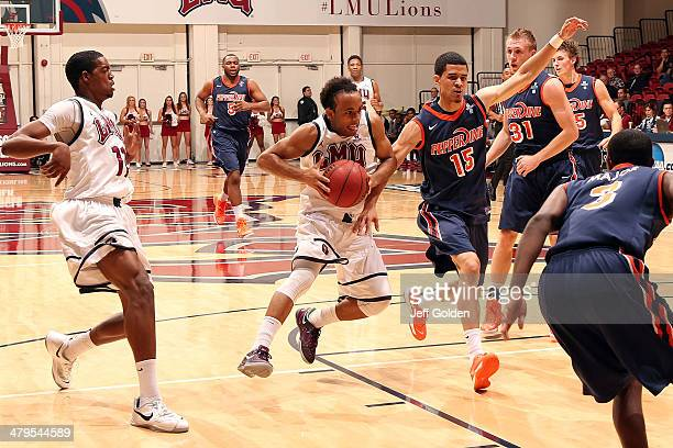 Evan Payne of the Loyola Marymount Lions drives while airborne on his way to making a layup against Malcolm Brooks of the Pepperdine Waves with 233...