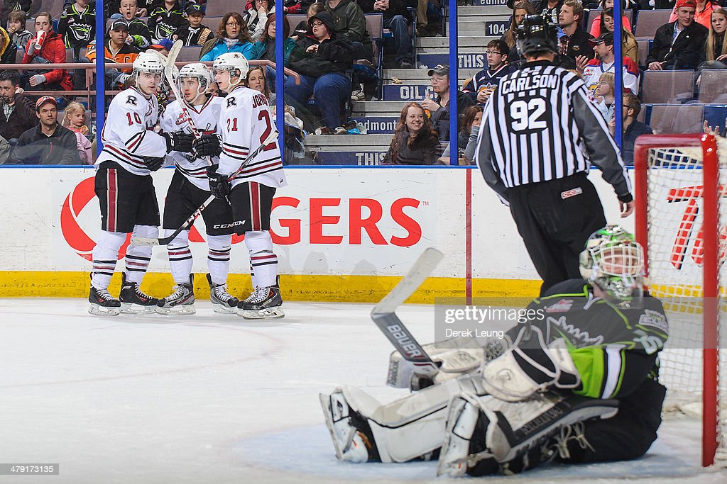Evan Polei #10, Rhyse Dieno #14, and Wyatt Johnson #21 of the Red Deer Rebels celebrate the goal of Dieno against Tyler Santos #35 of the Edmonton Oil Kings during a WHL game at Rexall Place on March 16, 2014 in Edmonton, Alberta, Canada. The Rebels defeated the Oil Kings 5-0.