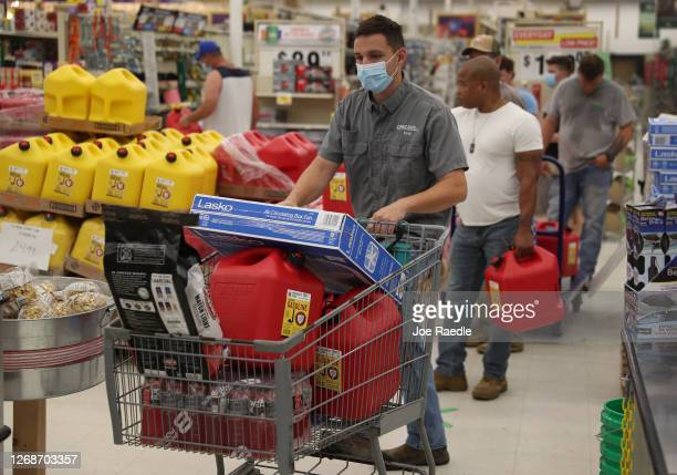 Evan Raggio and other people purchase supplies at the Stine hardware store before the possible arrival of Hurricane Laura on August 26, 2020 in Lake...