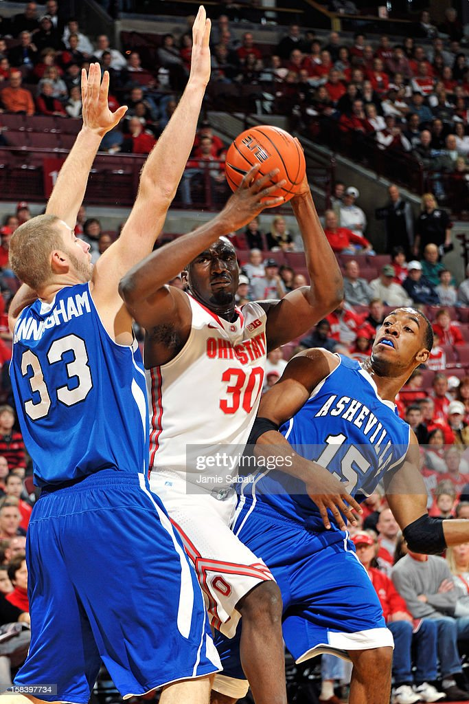 Evan Ravenel #30 of the Ohio State Buckeyes looks for room to shoot in the first half as D.J. Cunningham #33 and Jeremy Atkinson #15, both of the UNC Asheville Bulldogs, defend on December 15, 2012 at Value City Arena in Columbus, Ohio. Ohio State defeated UNC Asheville 90-72.