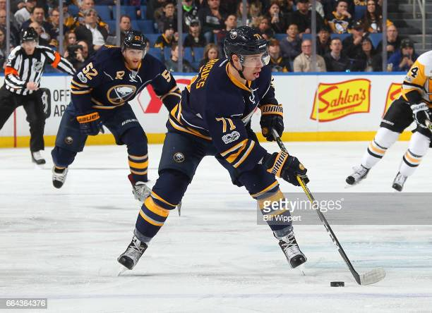 Evan Rodrigues and Hudson Fasching of the Buffalo Sabres skate against the Pittsburgh Penguins during an NHL game at the KeyBank Center on March 21...
