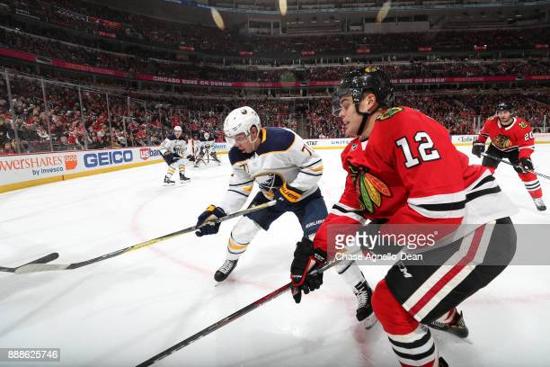 Evan Rodrigues of the Buffalo Sabres and Alex DeBrincat of the Chicago Blackhawks watch for the puck in the second period at the United Center on...