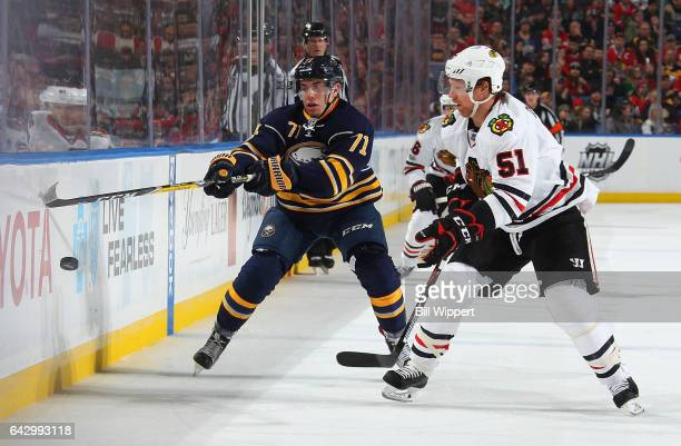 Evan Rodrigues of the Buffalo Sabres and Brian Campbell of the Chicago Blackhawks battle for the puck during an NHL game at the KeyBank Center on...