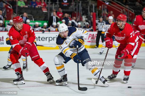 Evan Rodrigues of the Buffalo Sabres battles for the puck between Madison Bowey and Andreas Athanasiou of the Detroit Red Wings during an NHL game at...