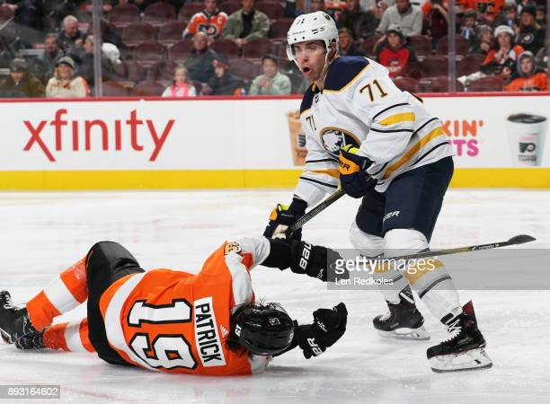 Evan Rodrigues of the Buffalo Sabres checks Nolan Patrick of the Philadelphia Flyers to the ice on December 14 2017 at the Wells Fargo Center in...