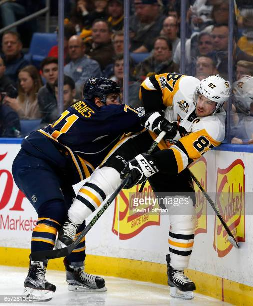Evan Rodrigues of the Buffalo Sabres checks Sidney Crosby of the Pittsburgh Penguins during the game at the KeyBank Center on March 21 2017 in...