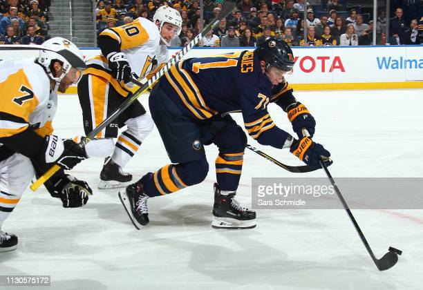 Evan Rodrigues of the Buffalo Sabres controls the puck against Matt Cullen and Garrett Wilson of the Pittsburgh Penguins during an NHL game on March...