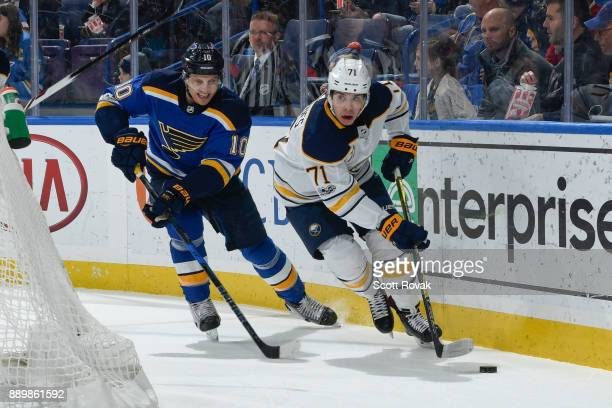 Evan Rodrigues of the Buffalo Sabres controls the puck as Brayden Schenn of the St Louis Blues pressures at Scottrade Center on December 10 2017 in...
