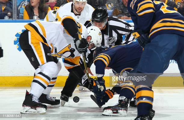 Evan Rodrigues of the Buffalo Sabres faces off against Garrett Wilson of the Pittsburgh Penguins during an NHL game on March 14 2019 at KeyBank...