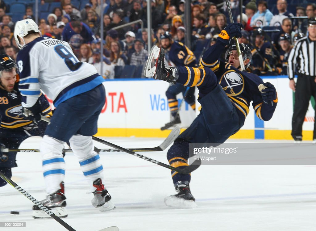 Evan Rodrigues #71 of the Buffalo Sabres is upended by Jacob Trouba #8 of the Winnipeg Jets during an NHL game on January 9, 2018 at KeyBank Center in Buffalo, New York. Winnipeg won, 7-4.