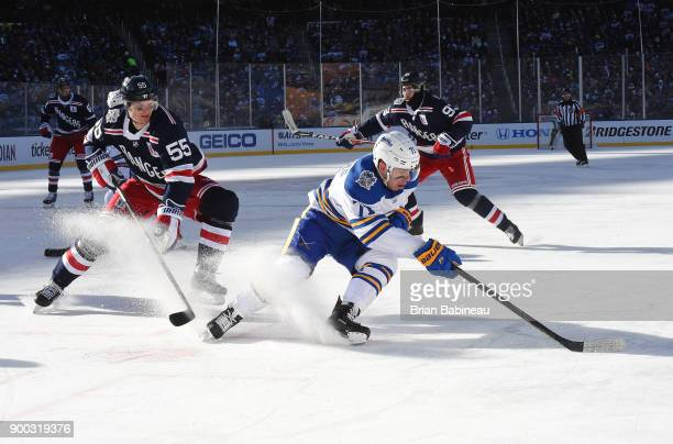 Evan Rodrigues of the Buffalo Sabres plays the puck away from Nick Holden of the New York Rangers during the first period of the 2018 Bridgestone NHL...