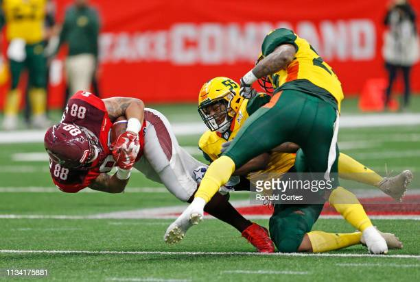 Evan Rodriguez of the San Antonio Commanders stretches for more yardage after a reception as he tries to elude Nyles Morgan of the Arizona Hotshots...