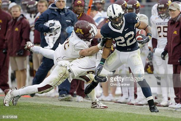 Evan Royster of the Penn State Nittany Lions is tackled by Kyle Theret and Marcus Sherels of the Minnesota Gophers at Beaver Stadium on October 17...