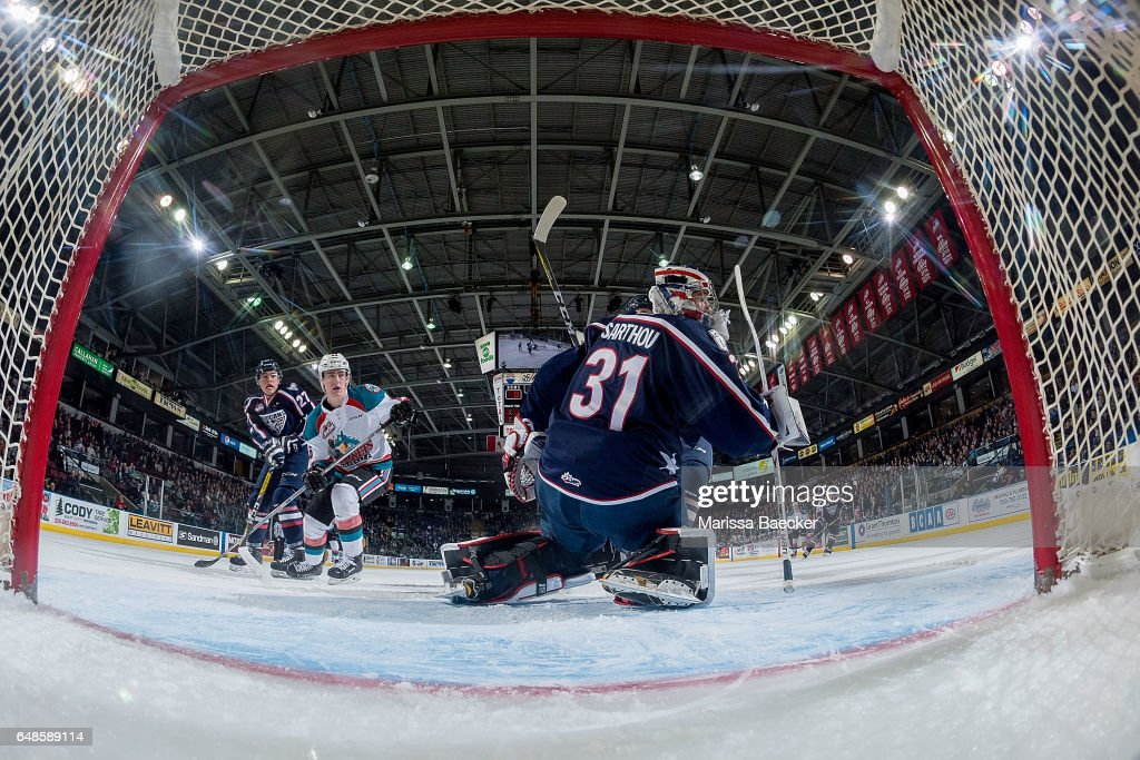 Evan Sarthou #31 of the Tri-City Americans defends the net as Kole Lind #16 of the Kelowna Rockets looks for the pass and a shot on net on March 4, 2017 at Prospera Place in Kelowna, British Columbia, Canada.