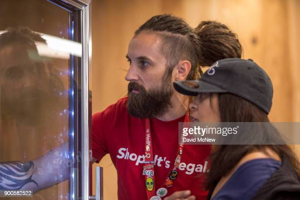Evan Seidlitz shows a customer refrigerated edibles at MedMen one of the two Los Angeles area pot shops that began selling marijuana for recreational...