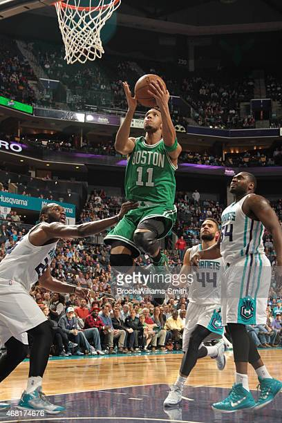 Evan Turner of the Boston Celtics shoots against Al Jefferson of the Charlotte Hornets during the game at the Time Warner Cable Arena on March 30...
