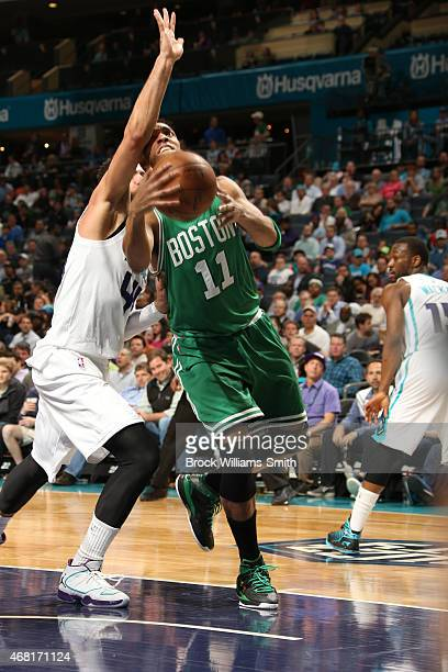 Evan Turner of the Boston Celtics shoots against Jeff Taylor of the Charlotte Hornets during the game at the Time Warner Cable Arena on March 30 2015...
