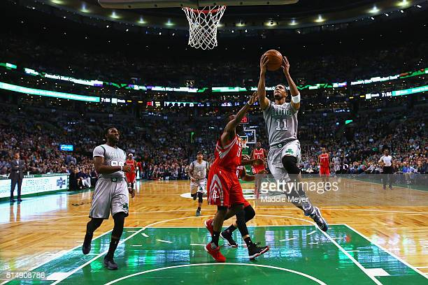 Evan Turner of the Boston Celtics takes a shot against James Harden of the Houston Rockets during the first half at TD Garden on March 11 2016 in...