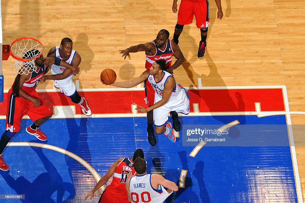 Evan Turner #12 of the Philadelphia 76ers drives to the basket against Emeka Okafor #50 of the Washington Wizards at the Wells Fargo Center on January 30, 2013 in Philadelphia, Pennsylvania.