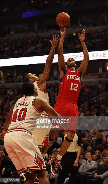 Evan Turner of the Philadelphia 76ers puts up a shot over Derrick Rose and Kurt Thomas of the Chicago Bulls at the United Center on December 21 2010...