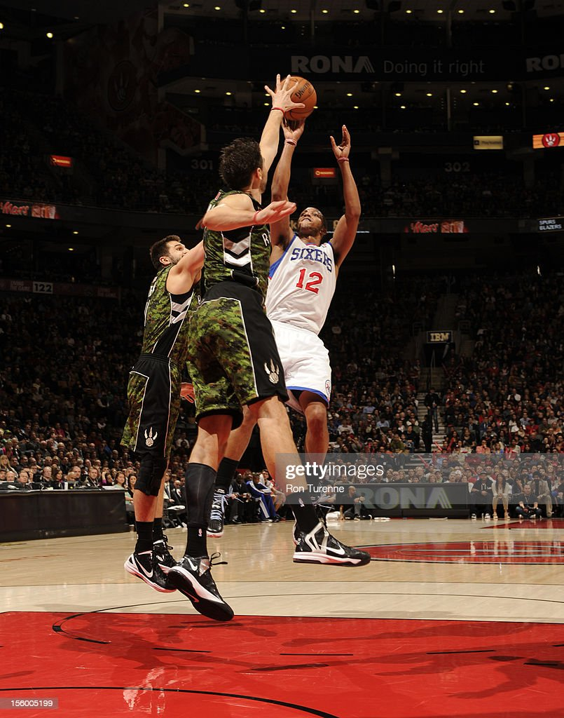 Evan Turner #12 of the Philadelphia 76ers shoots the ball over Toronto Raptors defenders during the game on November 10, 2012 at the Air Canada Centre in Toronto, Ontario, Canada.