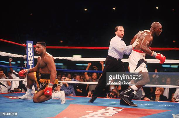 Evander Holyfield is guided away by the referee after knocking opponent Ray Mercer to his knees during a fight on May 20 1995 in Atlantic City New...