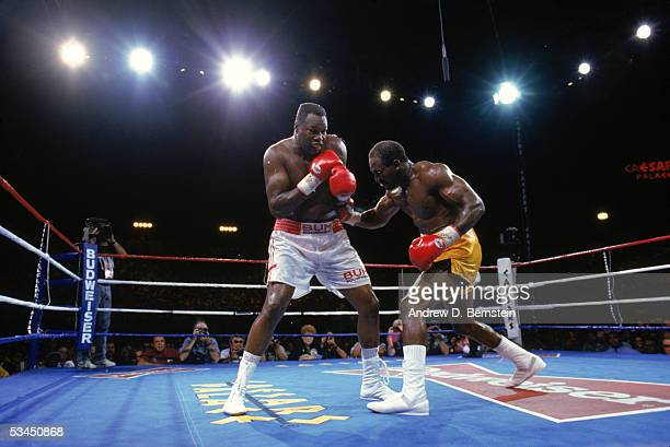 Evander Holyfield lands a right blow to Larry Holmes midsection as they compete for the WBC WBA IBF Heavyweight Titles in a bout schedule for twelve...