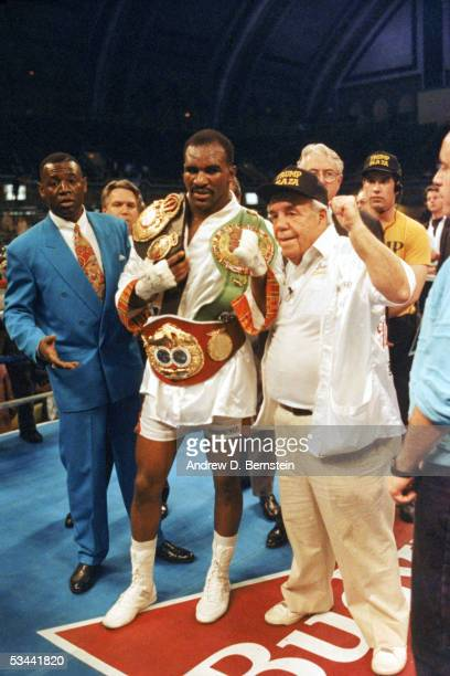 Evander Holyfield poses for a photo with his WBC WBA IBF Heavyweight championship Title belts after defeating George Foreman in a twelve round bout...