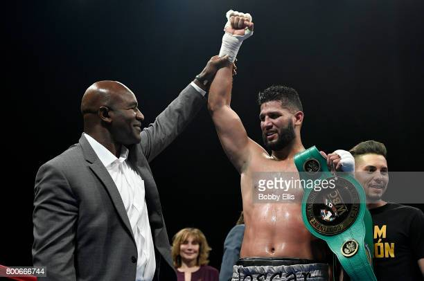 Evander Holyfield raises the hand of Carlos Negron after Negron defeated Derric Rossy in the WBC Continental Americas Heavyweight Championship at...