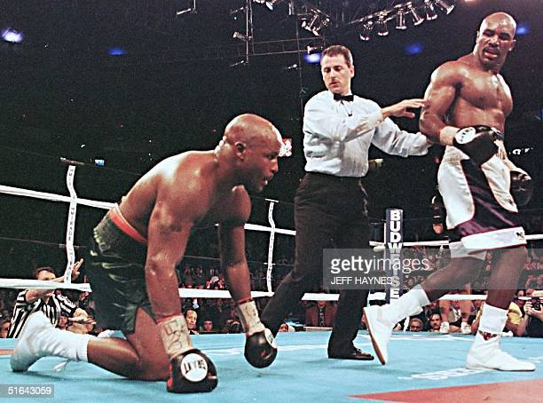 Evander Holyfield walks away after knocking down Michael Moorer in the seventh round of their WBA/IBF Heavyweight Championship Unification fight 08...