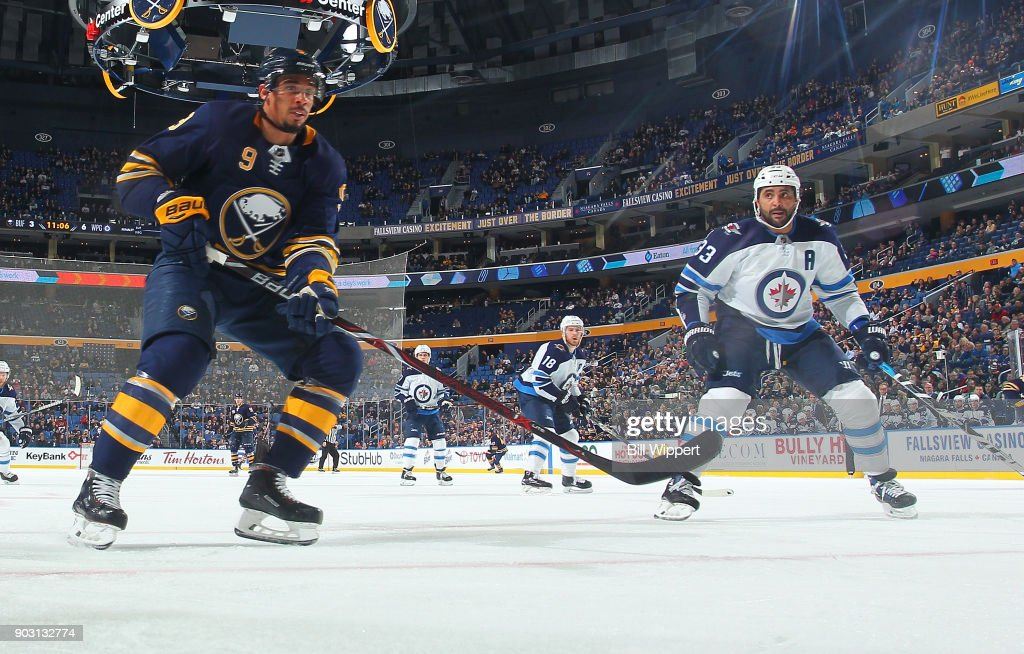 Evander Kane #9 of the Buffalo Sabres and Dustin Byfuglien #33 of the Winnipeg Jets keep an eye on play during an NHL game on January 9, 2018 at KeyBank Center in Buffalo, New York.