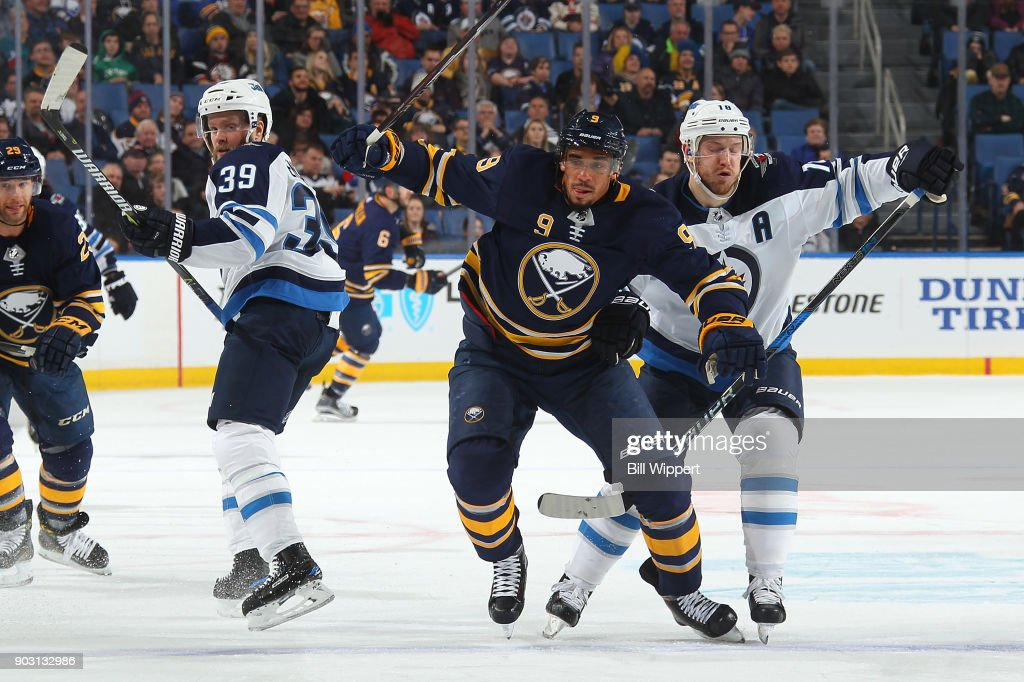 Evander Kane #9 of the Buffalo Sabres skates past Toby Enstrom #39 and Bryan Little #18 of the Winnipeg Jets during an NHL game on January 9, 2018 at KeyBank Center in Buffalo, New York. Winnipeg won, 7-4.