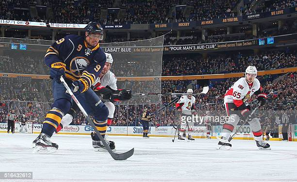 Evander Kane of the Buffalo Sabres skates with the puck against Marc Methot and Erik Karlsson of the Ottawa Senators during an NHL game on March 18...