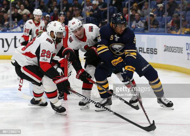Evander Kane of the Buffalo Sabres tries to take the puck around Matt Duchene and Johnny Oduya of the Ottawa Senators during the second period at the...