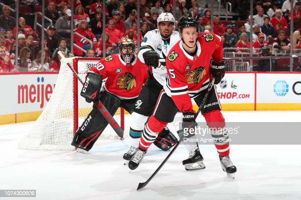 Evander Kane of the San Jose Sharks and Connor Murphy of the Chicago Blackhawks wait in position in front of goalie Corey Crawford in the first...