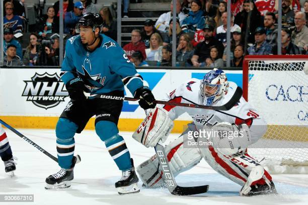 Evander Kane of the San Jose Sharks and Philipp Grubauer of the Washington Capitols watch for the puck at SAP Center on March 10 2018 in San Jose...