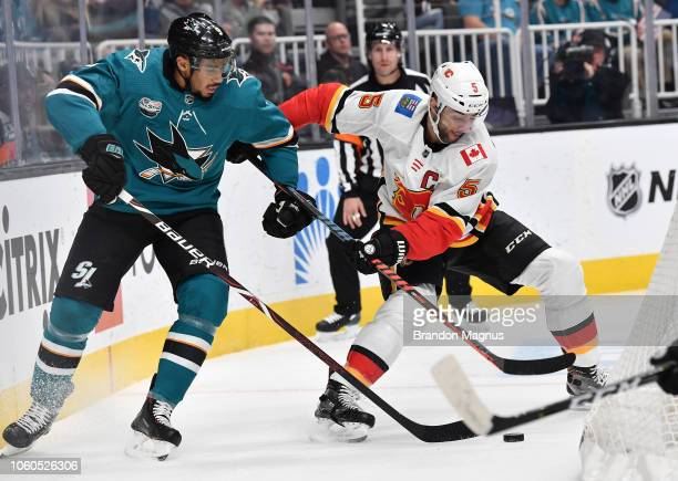Evander Kane of the San Jose Sharks battle for the puck with Mike Giordano of the Calgary Flames at SAP Center on November 11 2018 in San Jose...