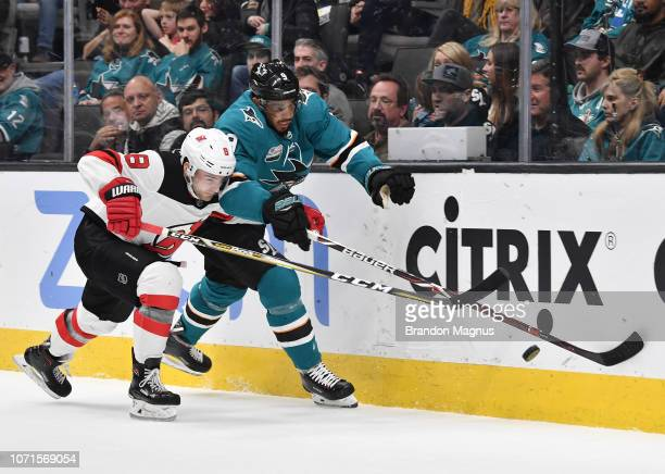 Evander Kane of the San Jose Sharks battles for the puck with Will Butcher of the New Jersey Devils at SAP Center on December 10 2018 in San Jose...