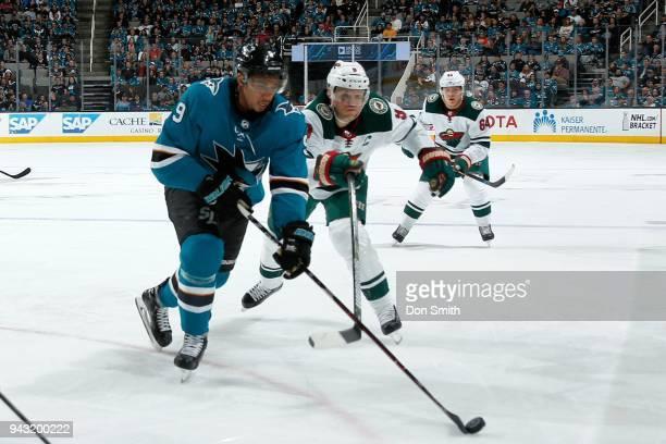 Evander Kane of the San Jose Sharks keeps the puck away from Mikko Koivu of the Minnesota Wild at SAP Center on April 7 2018 in San Jose California