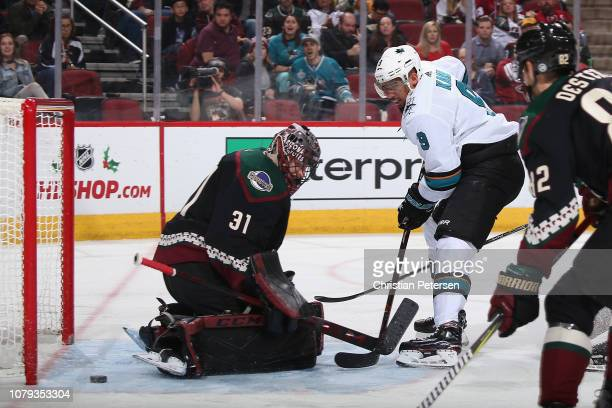 Evander Kane of the San Jose Sharks scores a goal past goaltender Adin Hill of the Arizona Coyotes during the second period of the NHL game at Gila...
