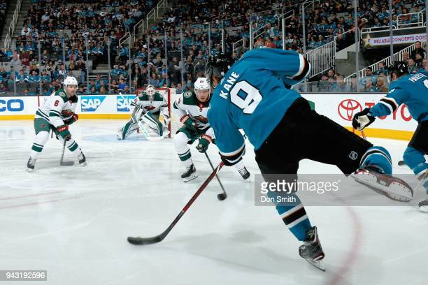 Evander Kane of the San Jose Sharks shoots the puck as Ryan Murphy Devan Dubnyk and Mikael Granlund of the Minnesota Wild defend at SAP Center on...